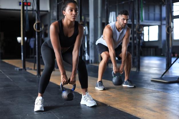 Un couple en forme et musclé s'est concentré sur le levage d'un haltère lors d'un cours d'exercice dans une salle de sport.