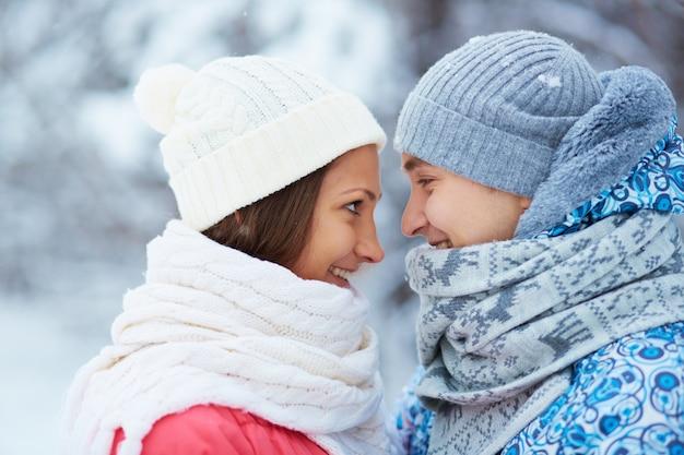 Couple avec des foulards et des chapeaux de laine regardant les uns les autres
