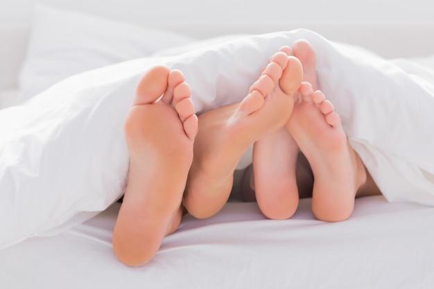 Couple frottant leurs pieds ensemble sous la couette