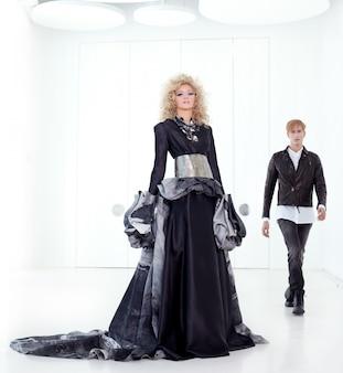 Couple futuriste rétro de haute couture noire dans une salle blanche moderne avec une inspiration de vampire