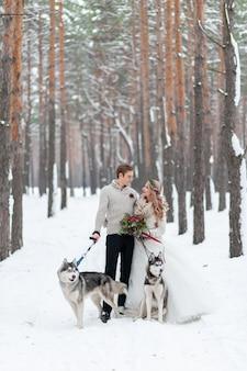 Couple gai joue avec un husky sibérien dans la forêt enneigée. mariage d'hiver.