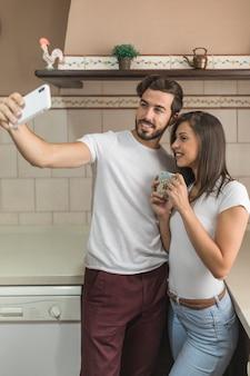 Couple gai posant pour selfie en cuisine
