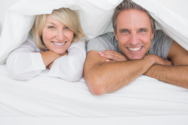 Couple gai souriant sous les couvertures à la caméra