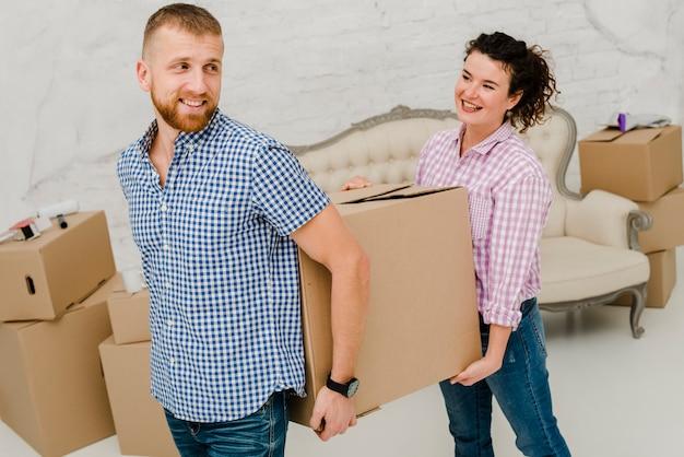 Couple gai transportant une grosse boîte