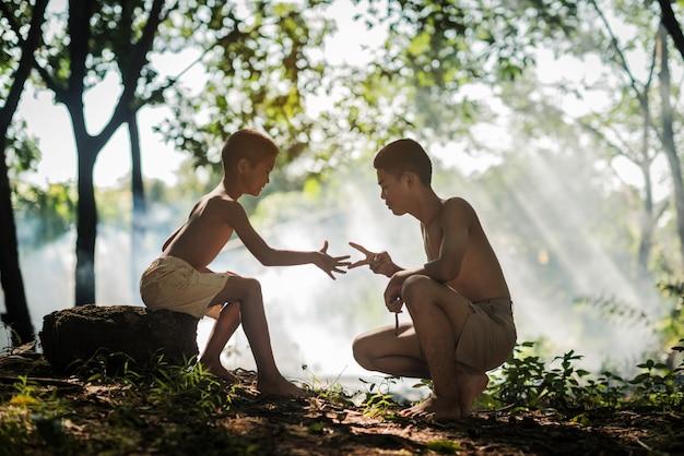 Couple garçon jouant la main symbole de bataille originaire de thaïlande. mode de vie campagne