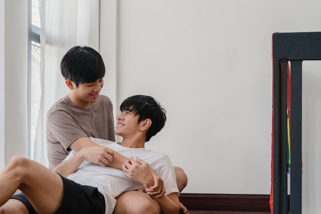 Couple gay asiatique couché et étreignant sur le sol à la maison. les jeunes lgbtq + asiatiques s'embrassant heureux se détendent se reposent ensemble et passent un moment romantique dans le salon avec le drapeau arc-en-ciel dans la maison moderne du matin.