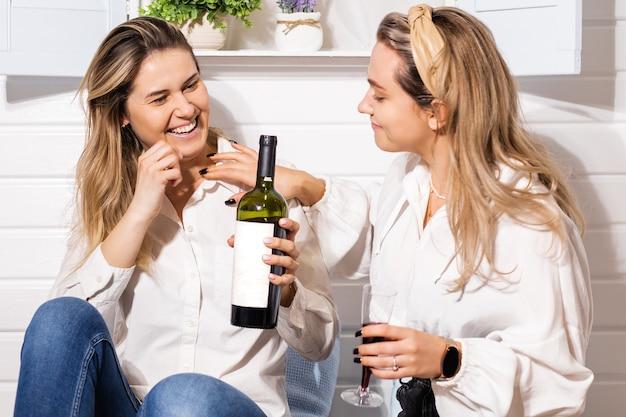 Couple gay deux belles jeunes femmes, fête romantique lgbt avec du vin rouge à la maison, bonheur, câlin, relation familiale