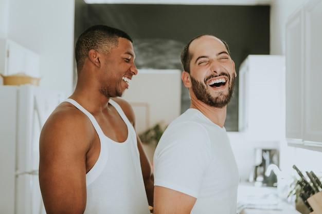 Couple gay embrassant dans la cuisine