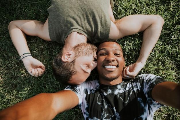 Couple gay se détendre dans l'herbe