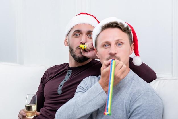 Couple gay soufflant cornes de fête célébrant noël à la maison