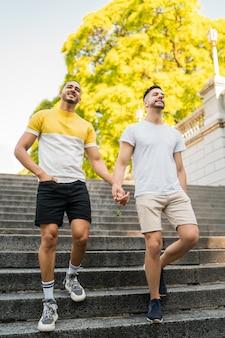Couple gay tenant leurs mains et marchant.