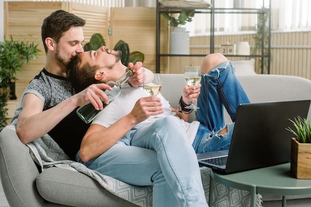 Couple de gays ayant un verre de vin blanc dans leur salon