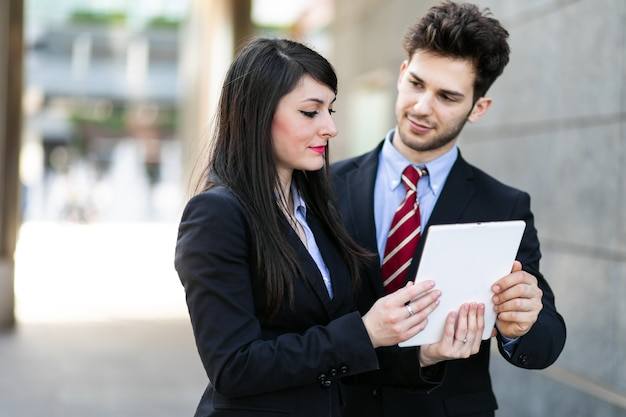 Couple de gens d'affaires à l'aide d'une tablette en plein air