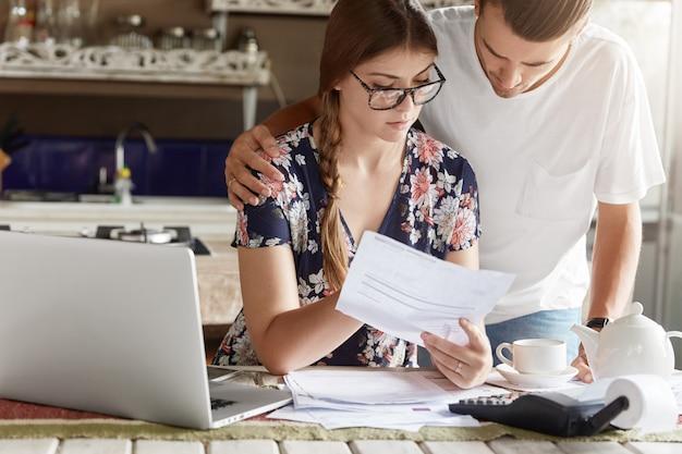 Couple gérant le budget ensemble dans la cuisine