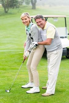 Couple golf mettant la balle ensemble souriant à la caméra