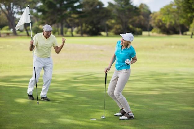 Couple de golfeurs matures célèbre le succès