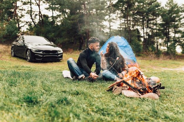 Couple goûte la guimauve cuite sur le feu