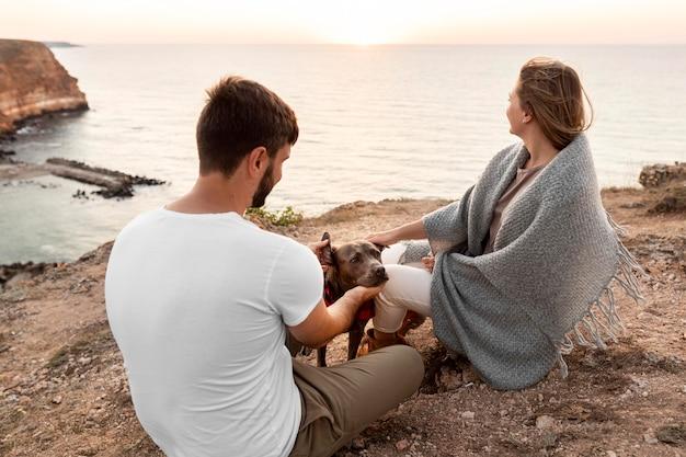 Couple grand angle en regardant le coucher du soleil avec leur chien