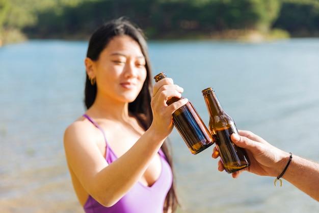 Couple, grillage, bouteilles bière