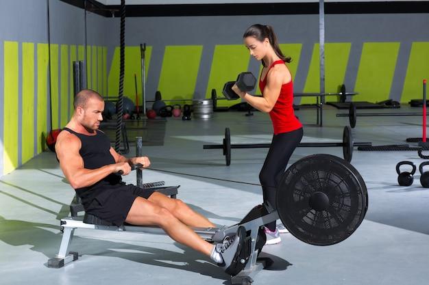 Couple de gym avec haltères et rameur de fitness