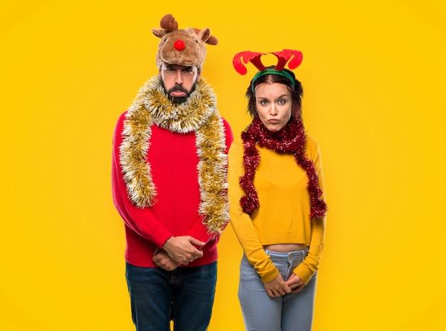 Couple habillé pour les vacances de noël avec une expression triste et déprimée.