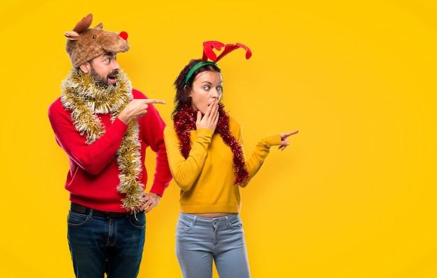 Couple habillé pour les vacances de noël, pointant le doigt sur le côté avec une surprise