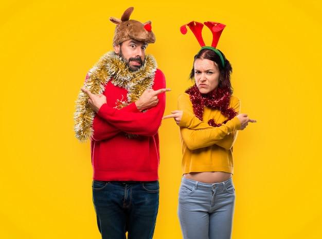 Couple habillé pour les vacances de noël, pointant vers les latéraux ayant des doutes