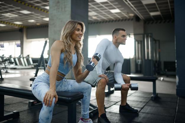 Couple avec haltères, entraînement physique en salle de sport