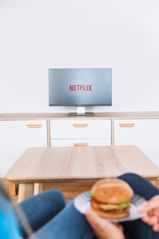Couple avec hamburger en regardant la série télévisée
