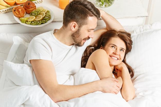 Couple hétérosexuel jeune adulte allongé sur le lit dans la chambre