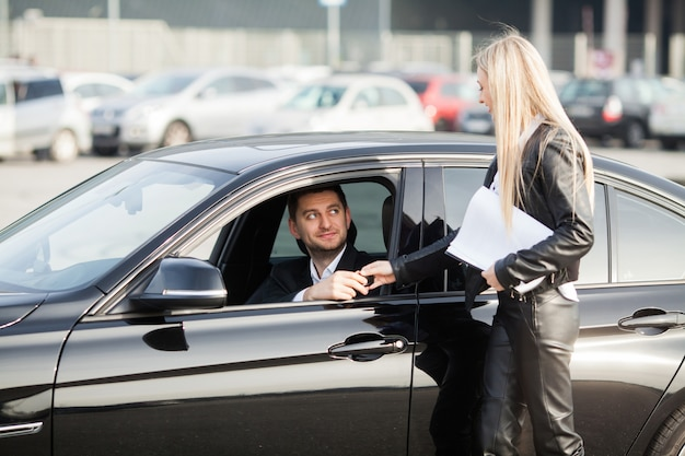 Couple heureux acheter une nouvelle voiture noire moderne
