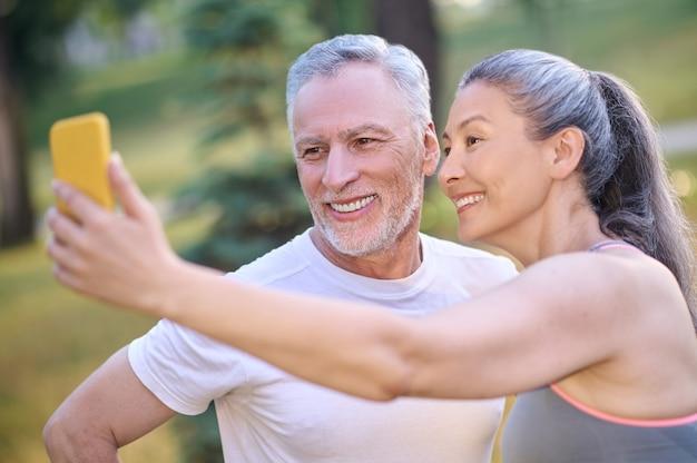 Un couple heureux d'âge mûr faisant un selfie et semblant satisfait