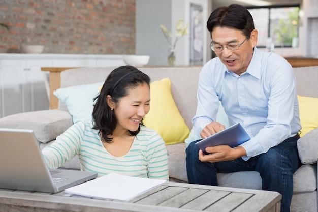 Couple heureux à l'aide d'un ordinateur portable et d'une tablette dans le salon