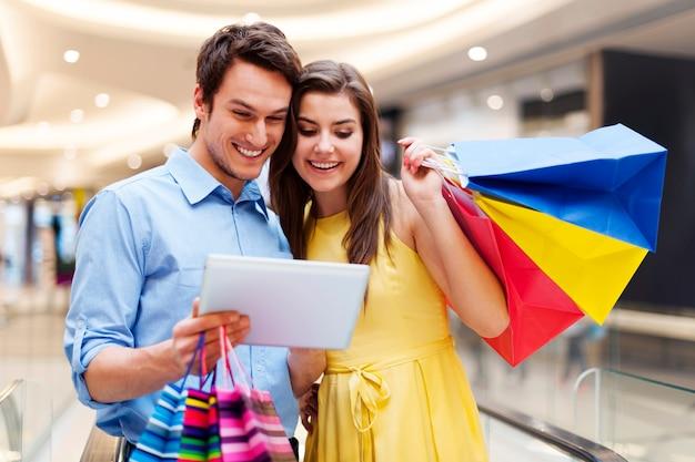 Couple heureux à l'aide de s tablette numérique dans le centre commercial
