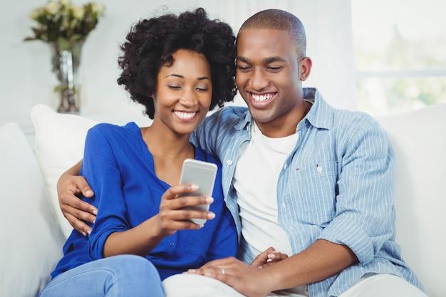 Couple heureux à l'aide de smartphone sur le canapé