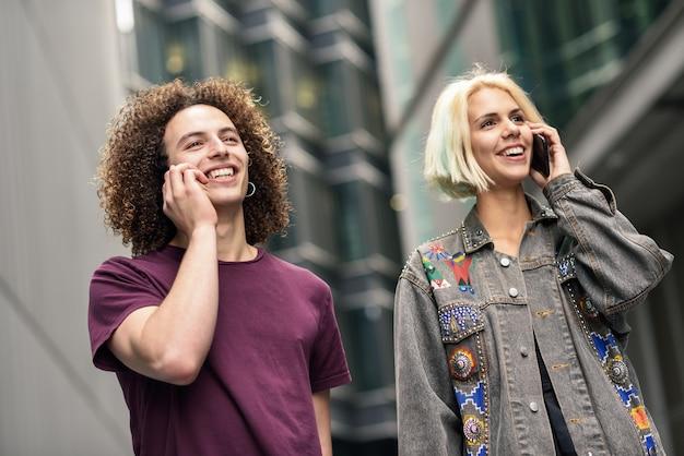 Couple heureux à l'aide de smartphone en contexte urbain.