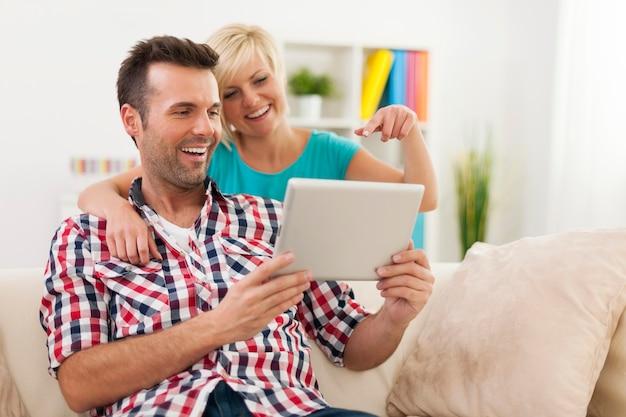 Couple heureux à l'aide de tablette numérique à la maison