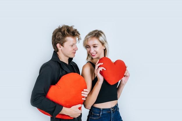 Couple heureux aimer ensemble tenant un coeur rouge