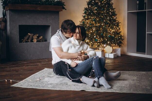 Couple heureux en amour assis à côté d'un arbre de noël à la maison