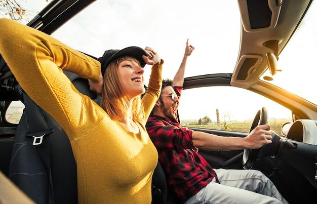 Couple heureux en amour au volant d'une voiture décapotable au coucher du soleil sur la route