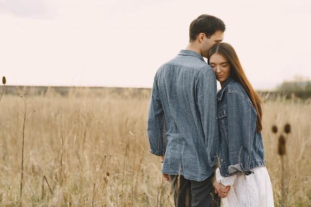 Couple heureux en amour dans le champ de blé au coucher du soleil