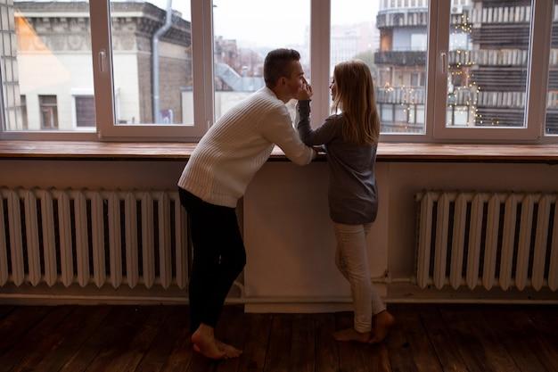 Couple heureux en amour embrasse et s'amuse debout près de la fenêtre dans leur chambre