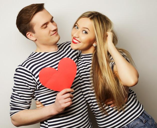 Couple heureux en amour tenant coeur rouge