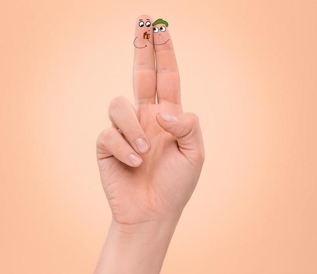 Un couple heureux amoureux des visages peints sur les doigts. le concept de la saint-valentin heureuse