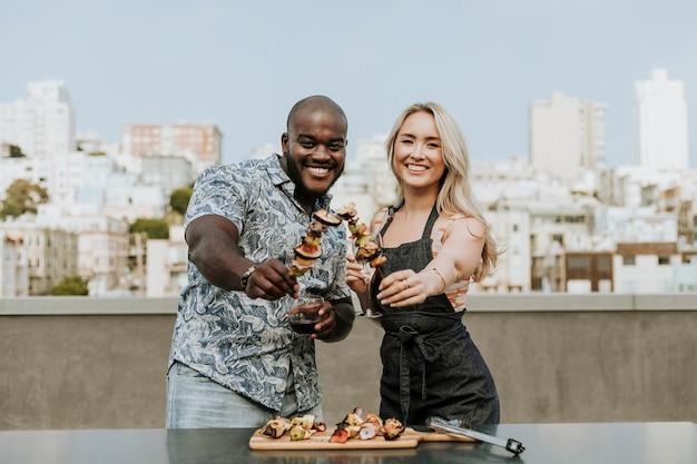 Couple heureux en appréciant une brochette de barbecue et un verre de vin