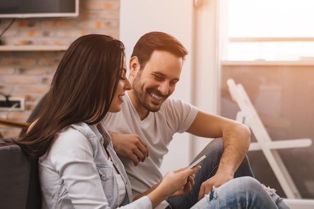 Couple heureux, appréciant le contenu multimédia dans un téléphone intelligent, assis sur le sol