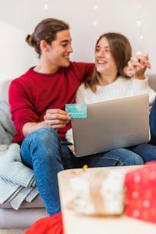 Couple heureux assis avec un ordinateur portable sur un canapé