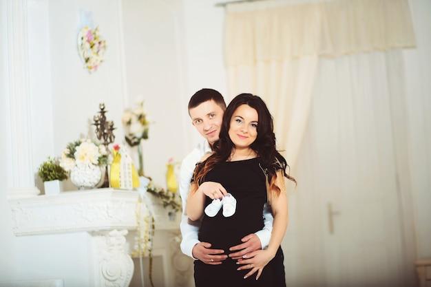 Couple heureux en attente de bébé, belle femme enceinte et son mari gai tenant en mains de minuscules bottes mignonnes pour leur futur enfant, nouveau concept de vie