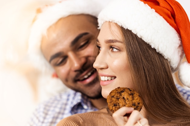 Couple heureux attrayant gai dans des chapeaux de santa