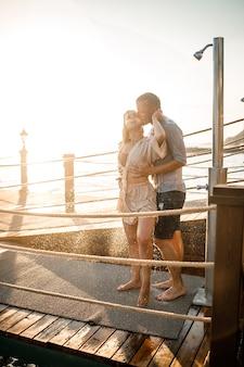 Couple heureux au bord de la mer. un gars et une fille sont sous la douche sur une jetée à ciel ouvert. couple heureux en vacances. homme et femme au bord de la mer.